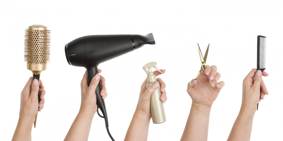 Human hands holding various hairdressing tools isolated on white background