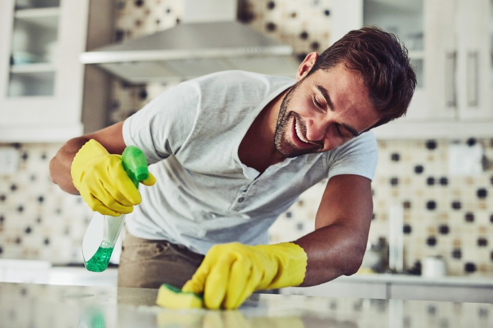 Shot of a handsome young man cleaning his home