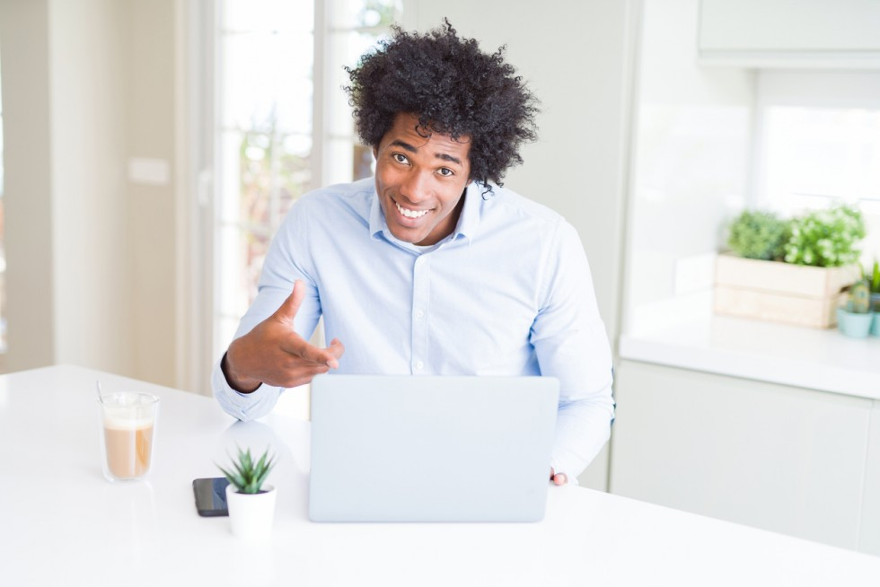 African American business man working using laptop very happy pointing with hand and finger