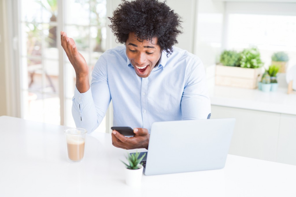 African American business man using smartphone and laptop very happy and excited, winner expression celebrating victory screaming with big smile and raised hands