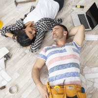 Couple lying on the floor in new home, looking at each other.