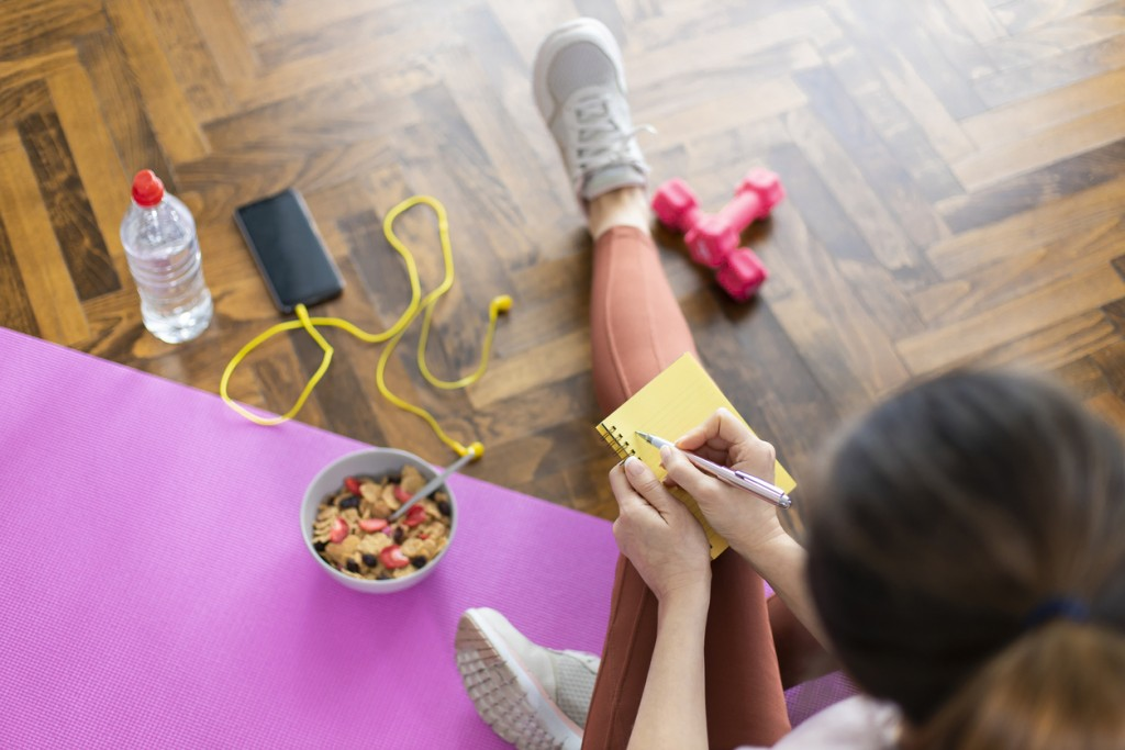 Young sporty woman writing workout plan in notebook after a workout