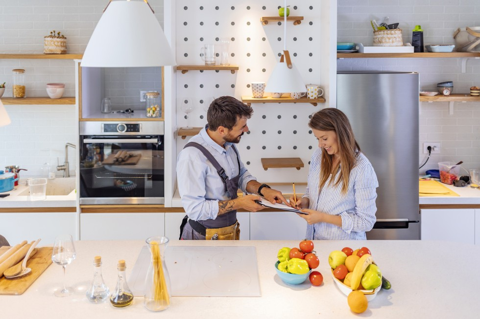 Happy Woman Writing On Clipboard In Front Of Young Plumber Standing In Kitchen, signing Invoice From Male Plumber In Kitchen